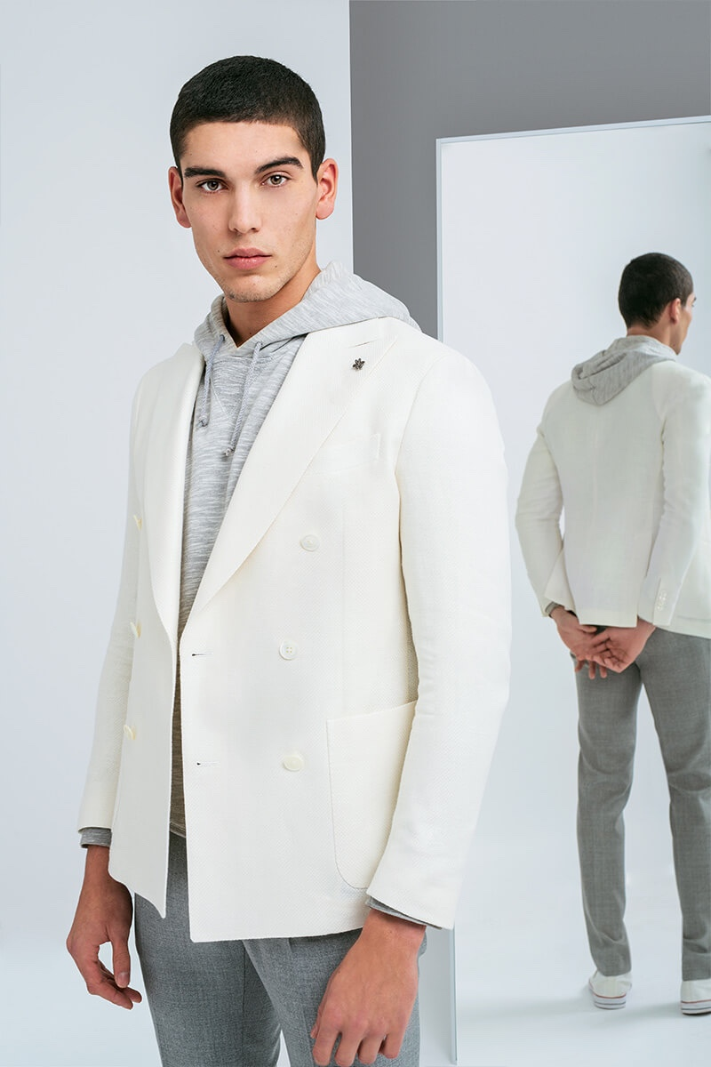 A fresh vision, Samuele Urbani sports a cream double-breasted jacket with a gray marle hoodie and pleated trousers for Lubiam's spring-summer 2020 campaign.
