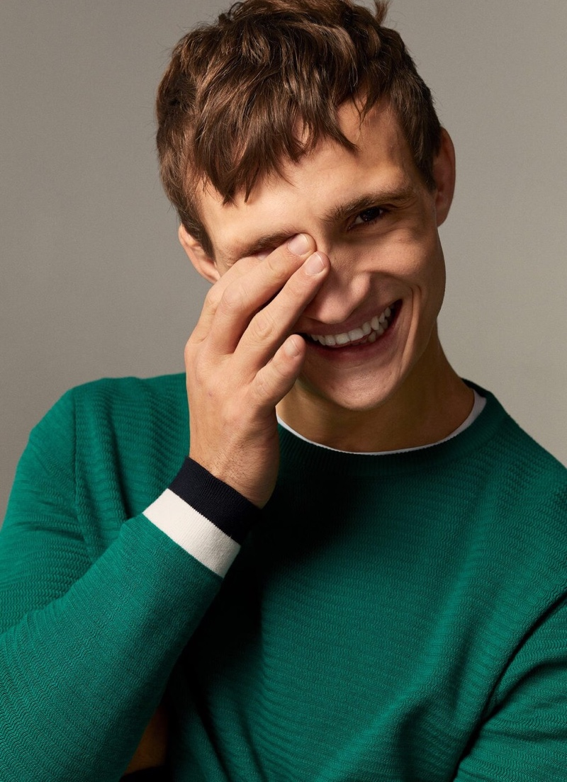 All smiles, Julian Schneyder rocks a green sweater from Mango.