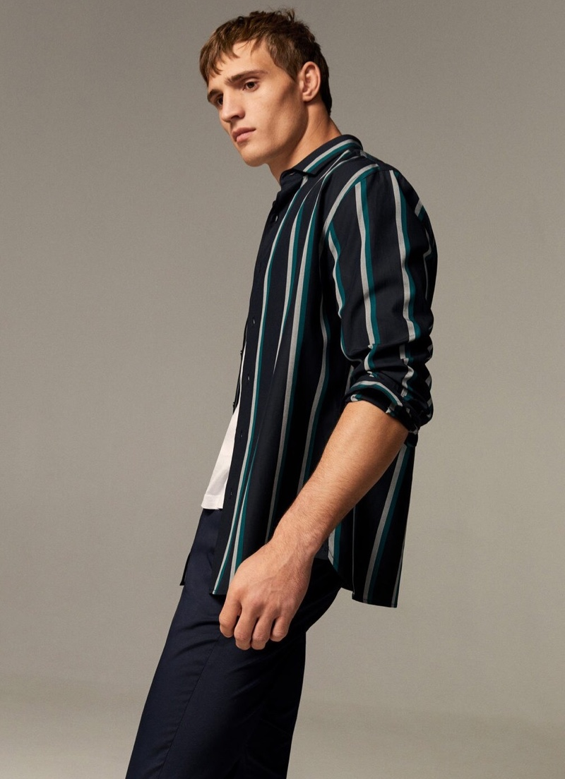 Front and center, Julian Schneyder sports a striped button-down shirt.