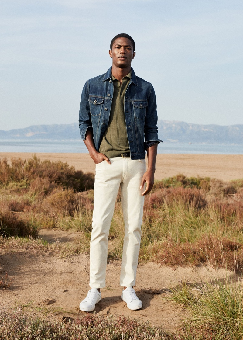 Donning a jean jacket with a smart polo and white pants, Hamid Onifade wears Mango.