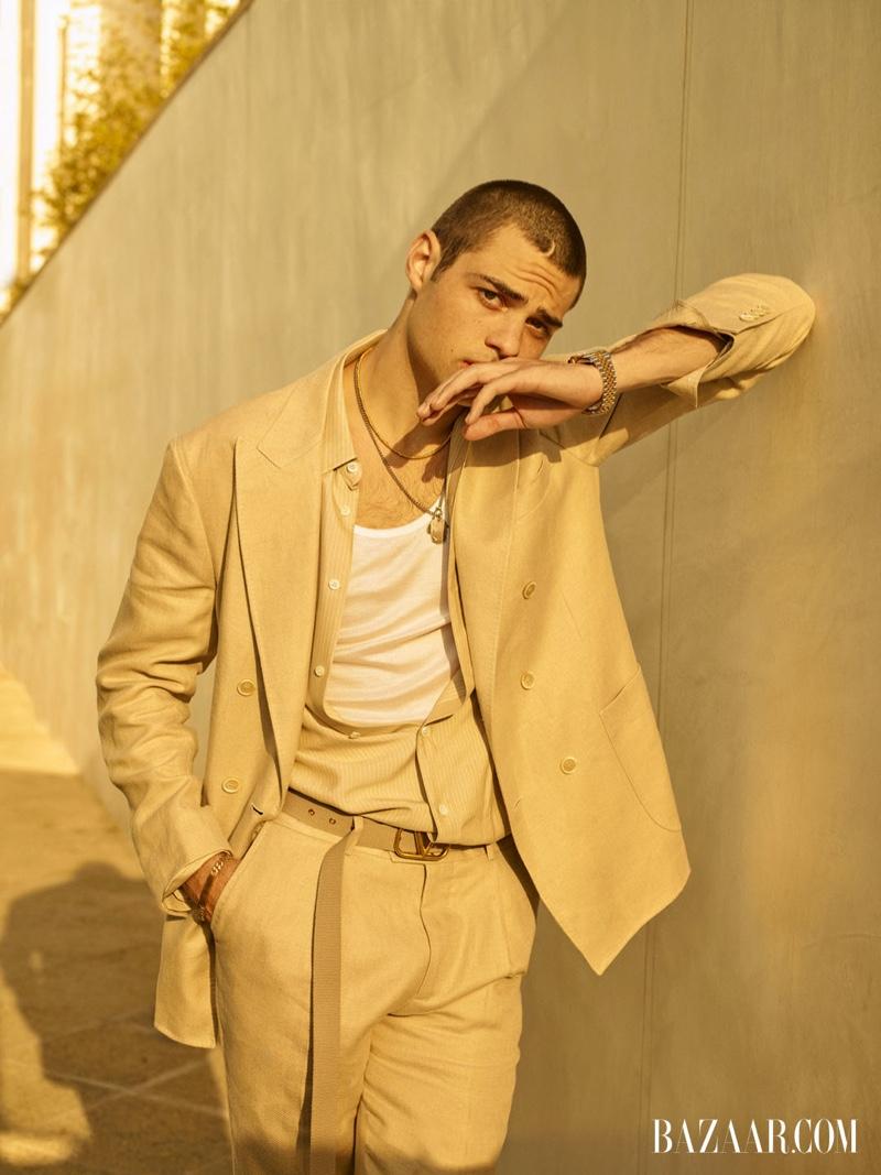 Embracing neutrals, Noah Centineo wears a Brunello Cucinelli suit, Valentino belt, Eli Halili necklace, Pyrrha ring, Rolex watch, Tiffany & Co. bracelet, Celine shirt and tank for Harper's Bazaar Men's.