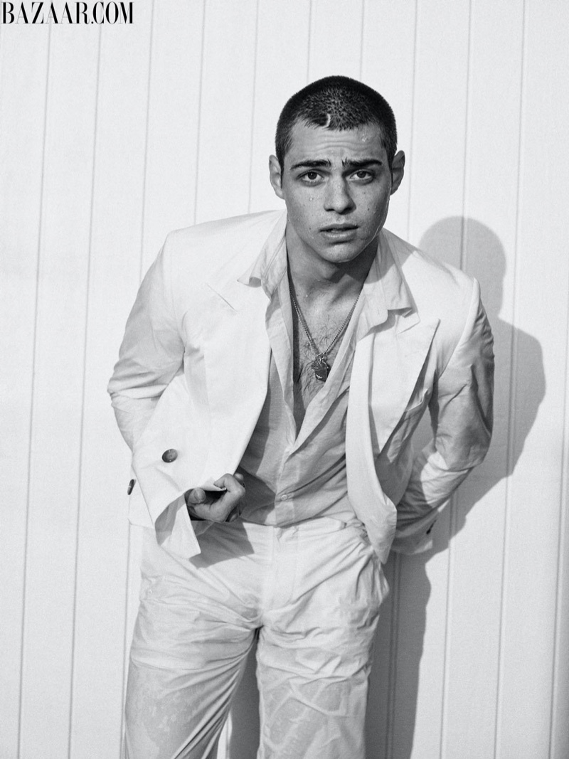 Clad in white, Noah Centineo sports a Hugo Boss suit, Sandro top, Pyrrha ring, and Tiffany & Co. bracelet for Harper's Bazaar Men's.