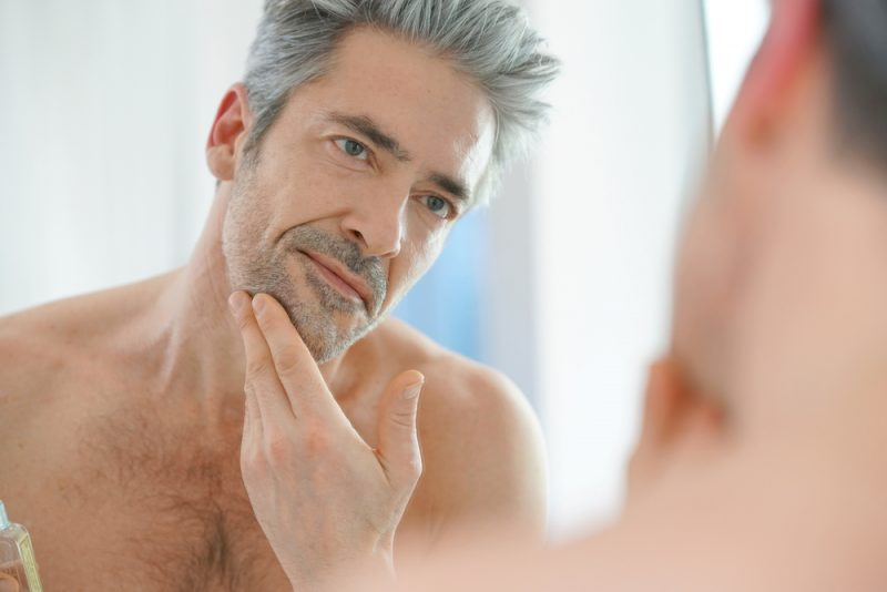 Older Man Looking in Mirror with Gray Hair