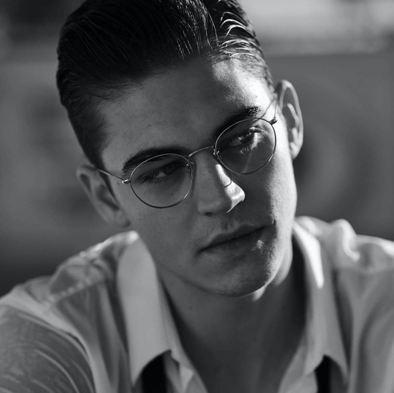Appearing in a black and white photo, Hero Fiennes-Tiffin sports glasses for Oliver Peoples' spring-summer 2020 campaign.