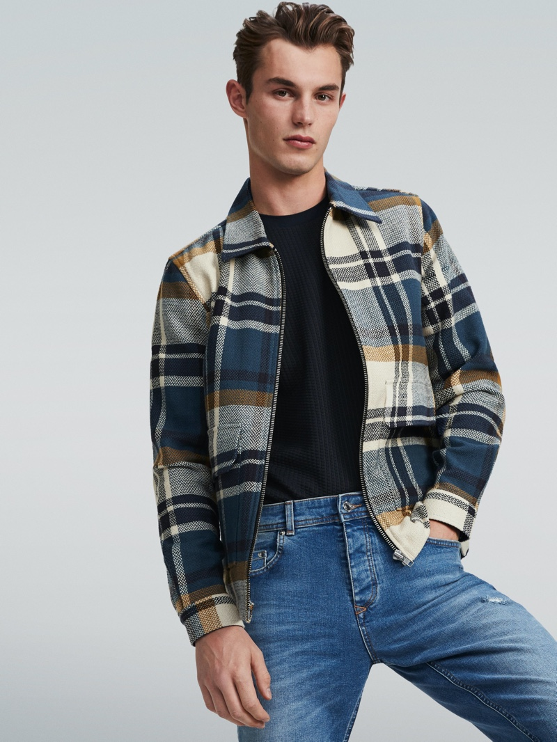 Kit Butler rocks a checked jacket and denim jeans for River Island's spring 2020 campaign.