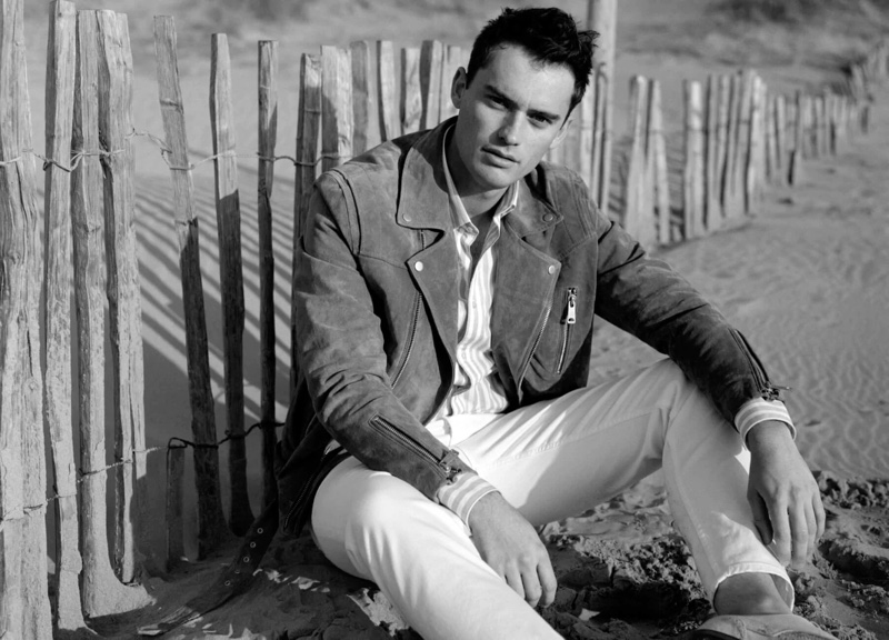 Relaxing at the beach, Harrison Griffiths sports a Scotch & Soda suede biker jacket in pecan.