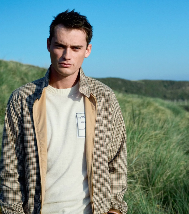 Pictured outdoors, Harrison Griffiths wears a reversible Harrington jacket by Scotch & Soda.