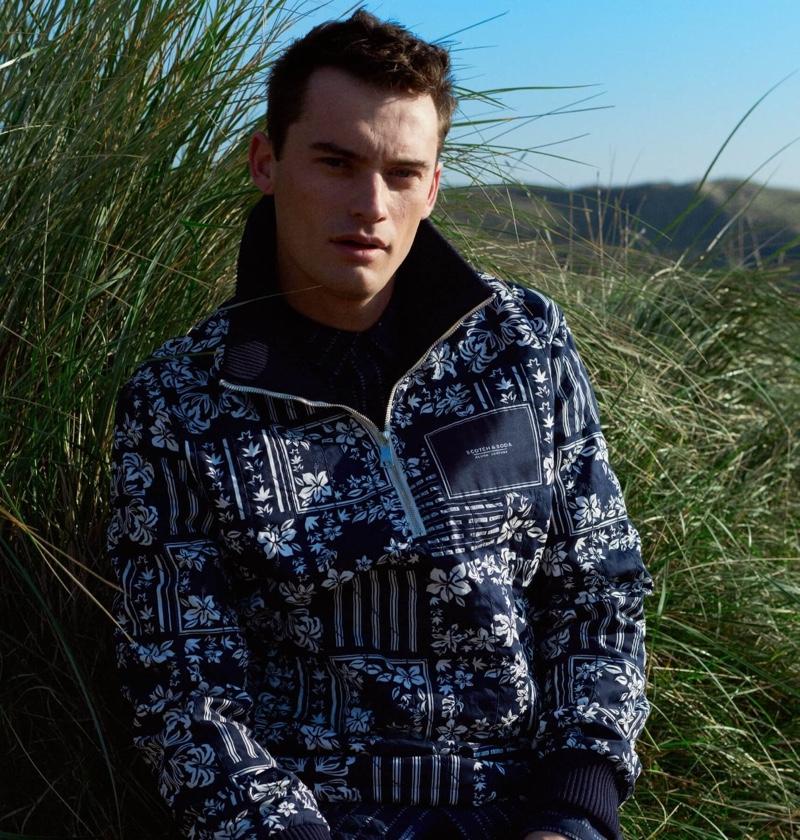 Model Harrison Griffiths sports a Scotch & Soda printed sweater jacket.