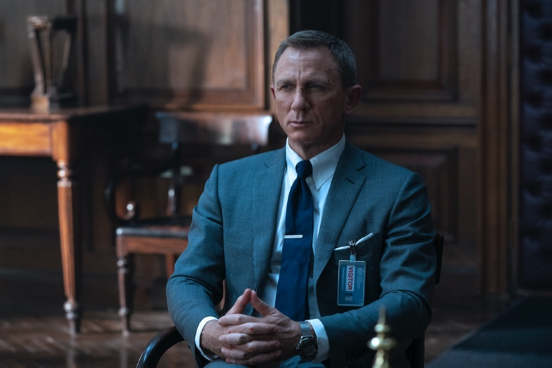 Portraying James Bond in No Time to Die, Daniel Craig wears a Tom Ford dark blue wool-silk check O'Connor notch lapel jacket and tailored trousers. He accessorizes with a Tom Ford sky blue poplin collared shirt and dark blue diagonal silk tie. | Photo courtesy of Tom Ford | Photo Credit: Nicola Dove © 2020 Danjaq, LLC, and MGM. All Rights Reserved.