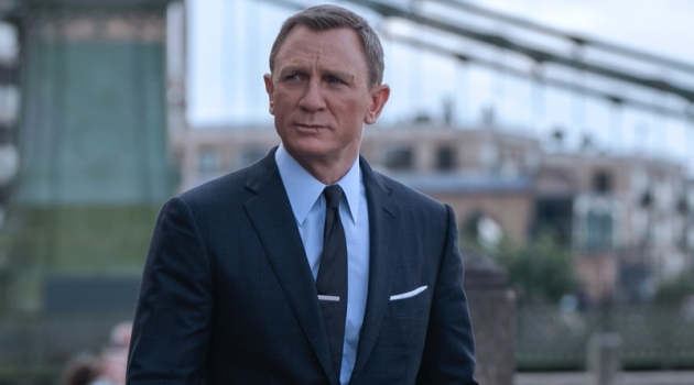Daniel Craig suits up as James Bond once more in No Time to Die. He wears a Tom Ford grey wool Prince of Wales check O'Connor notch lapel jacket and tailored trousers. A Tom Ford sea island poplin collared shirt and off white silk pocket square complete his look. | Photo courtesy of Tom Ford | Photo Credit: Nicola Dove © 2020 Danjaq, LLC and MGM. All Rights Reserved.