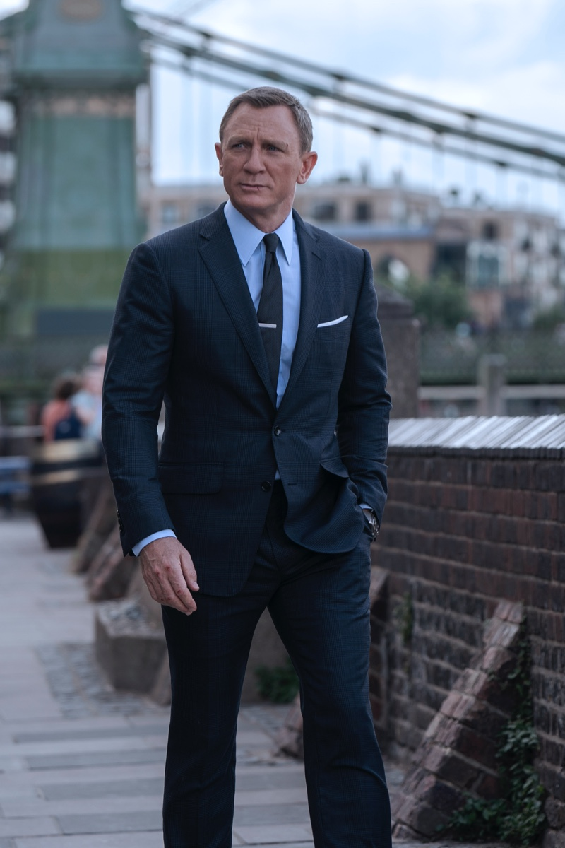 Daniel Craig suits up as James Bond once more in No Time to Die. He wears a Tom Ford grey wool Prince of Wales check O'Connor notch lapel jacket and tailored trousers. A Tom Ford sea island poplin collared shirt and off white silk pocket square complete his look. | Photo courtesy of Tom Ford | Photo Credit: Nicola Dove © 2020 Danjaq, LLC, and MGM. All Rights Reserved.