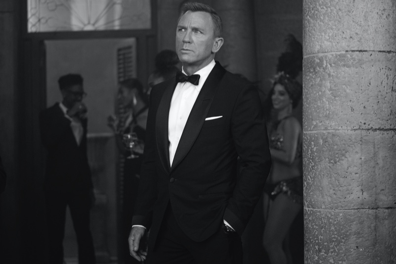 Dressed to impress, Daniel Craig returns as James Bond in No Time to Die. Craig dons a Tom Ford black wool Atticus shawl collar cocktail jacket with quilted satin lapel and cuffs. A dapper vision, Craig wears Tom Ford Atticus evening trousers, a white poplin collared shirt, satin self bowtie, and off white silk pocket square as well. | Photo courtesy of Tom Ford | Photo Credit: Nicola Dove © 2020 Danjaq, LLC, and MGM. All Rights Reserved.