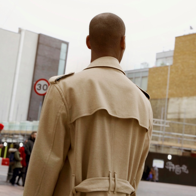 Connecting with Dolce & Gabbana, Sacha M'Baye dons a classic trench coat.