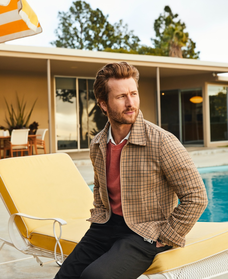 Glen Powell dons a checked Sandro jacket and white polo shirt for Bloomingdale's spring 2020 Mix Masters campaign. He also sports a Rag & Bone sweater and Barena pants.