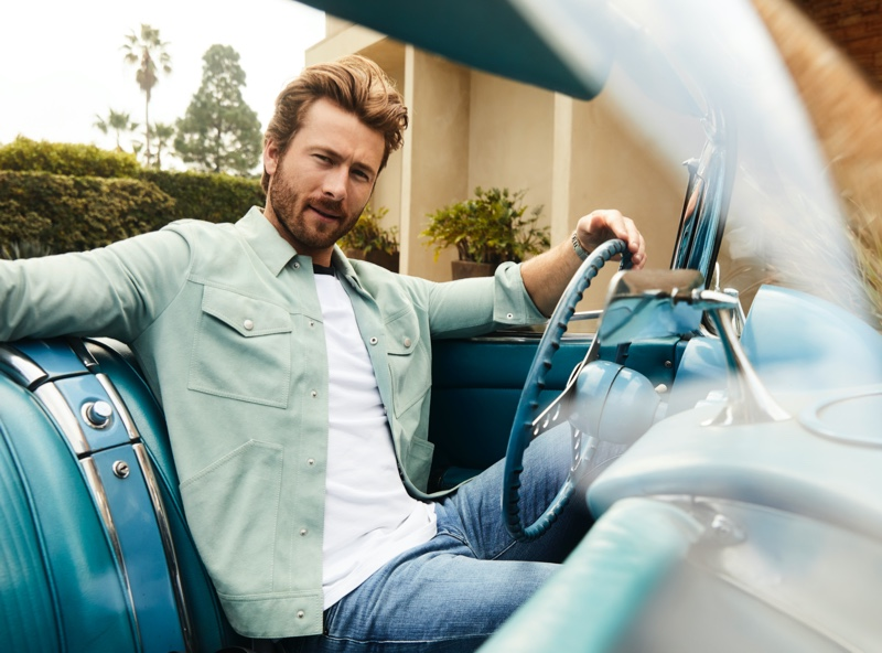Getting behind the wheel of a vintage car, Glen Powell wears a green Reiss trucker jacket, ATM shirt, and Frame jeans for Bloomingdale's spring 2020 Mix Masters campaign.