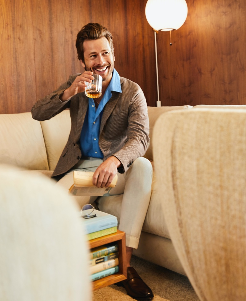 Enjoying a drink, Glen Powell wears an Edios seersucker blazer and linen shirt. Powell completes his look with Reiss pants and To Boot New York loafers for Bloomingdale's spring 2020 Mix Masters campaign.