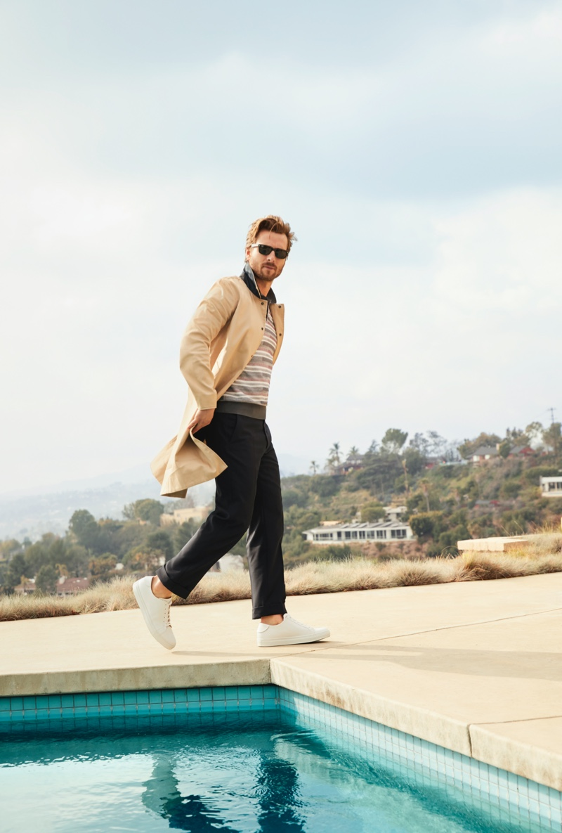 Making a case for classic style, Glen Powell sports a Rag & Bone trench coat, Z Zegna striped polo, Collegium white sneakers, and Ray-Ban sunglasses for Bloomingdale's spring 2020 Mix Masters campaign.