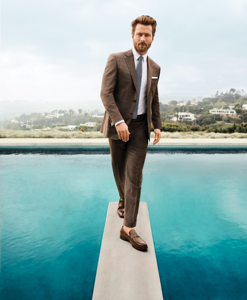 Pictured on a diving board, Glen Powell rocks a Canali brown suit, Z Zegna shirt, Ledbury tie, and To Boot New York loafers for Bloomingdale's spring 2020 Mix Masters campaign.