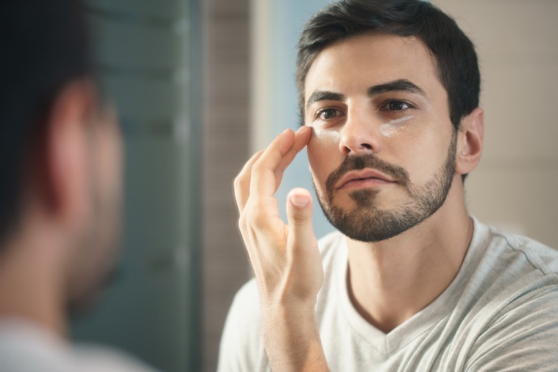 Hispanic Man Applying Face Cream Mirror Grooming