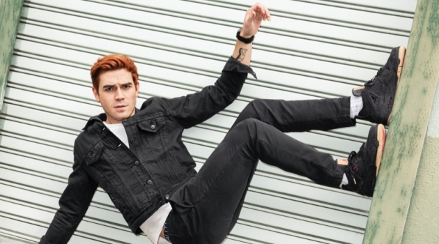 Turning his world side up, KJ Apa sports a Levi's denim jacket with a Velva Sheen t-shirt. Photographed for Men's Health, he also wears Gap jeans and Levi's x Air Jordan sneakers.