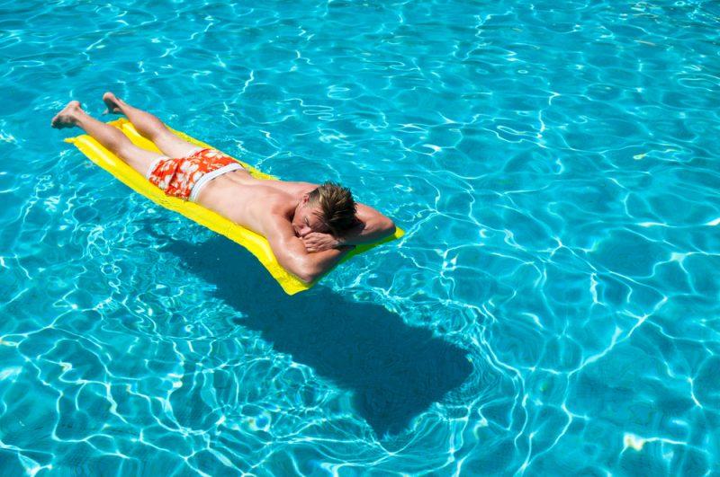 Man in Pool Wearing Swim Shorts