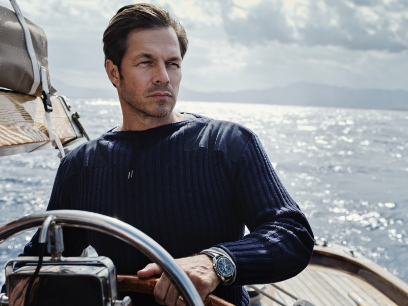 Model Paul Sculfor sports a navy ribbed army sweater by N. Peal that was designed for James Bond in No Time to Die.