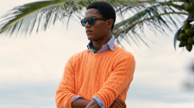 Hamid Onifade sports a bright orange cable-knit sweater with a striped oxford shirt and frayed white shorts by POLO Ralph Lauren.