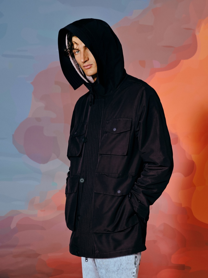 Model Aaron Shandel  makes a military-inspired statement in a hooded parka from Reserved's Re Design collection.