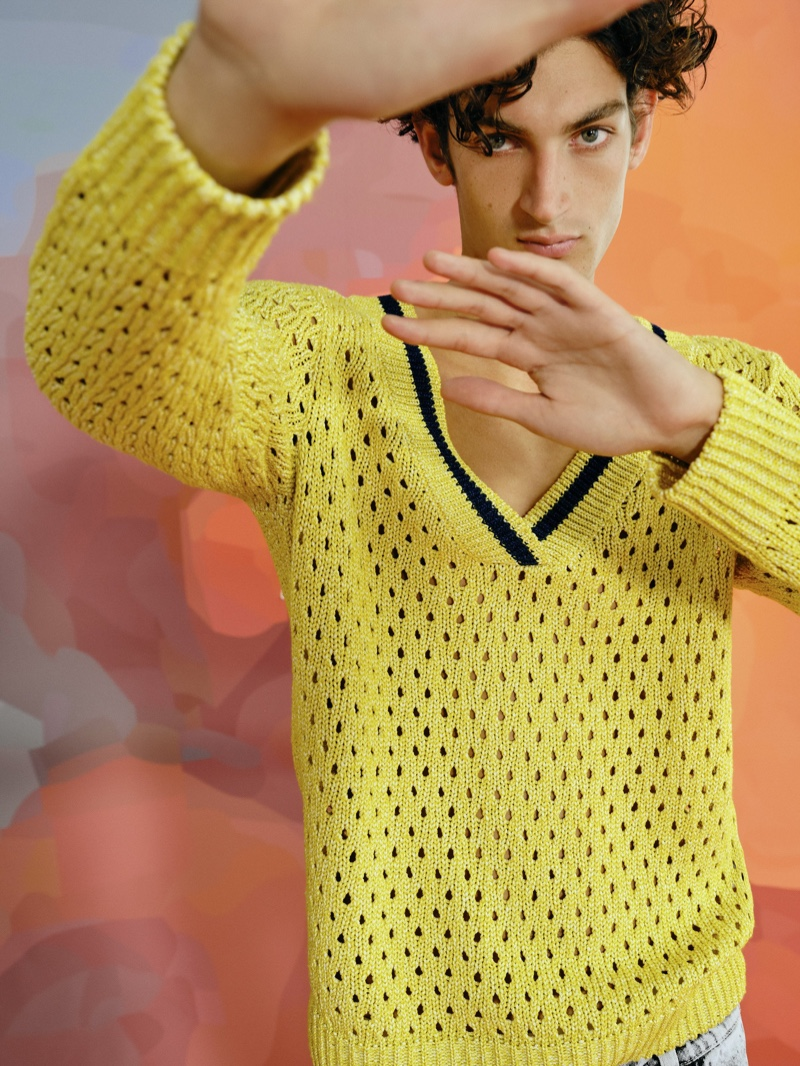 Making a colorful statement, Aaron Shandel sports Reserved's yellow oversized v-neck sweater from its Re Design collection.