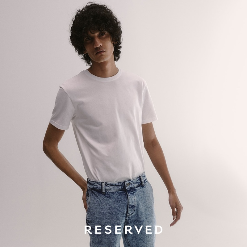Mustafa Dawood sports a white t-shirt with acid wash jeans from Reserved.