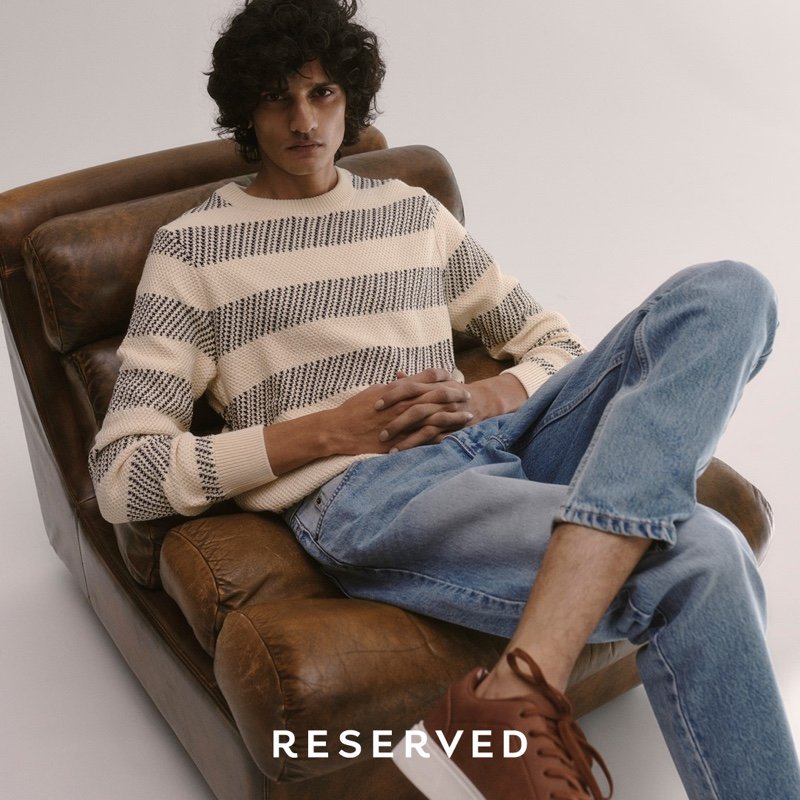 Reclining in a leather chair, Mustafa Dawood goes casual in a striped sweater and light wash denim jeans from Reserved.