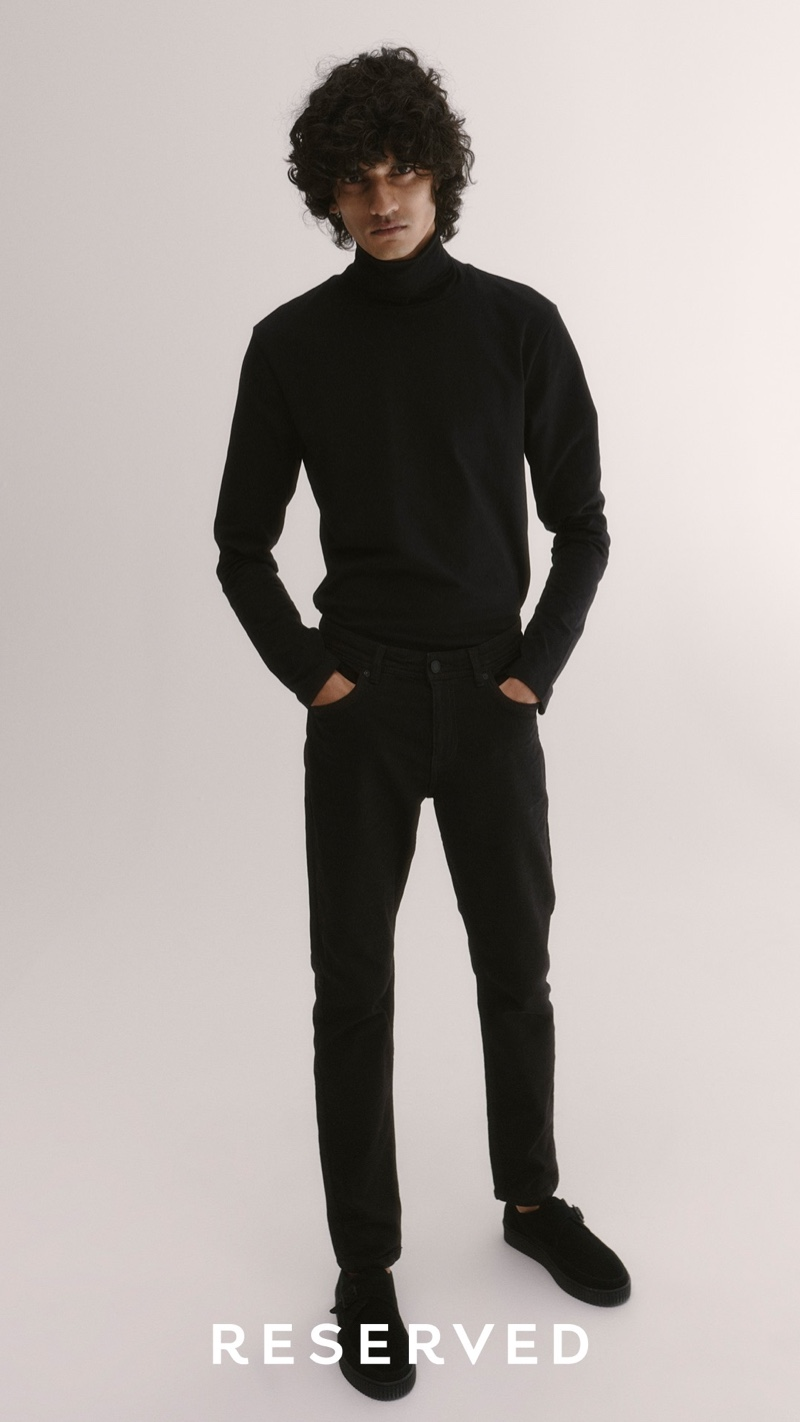 Wearing all black, Mustafa Dawood models a turtleneck with jeans from Reserved.