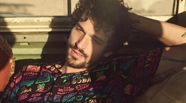 Enjoying a warm day's sun, Paul Kelly appears in Scotch & Soda's spring-summer 2020 campaign. He relaxes in the brand's printed viscose shirt.