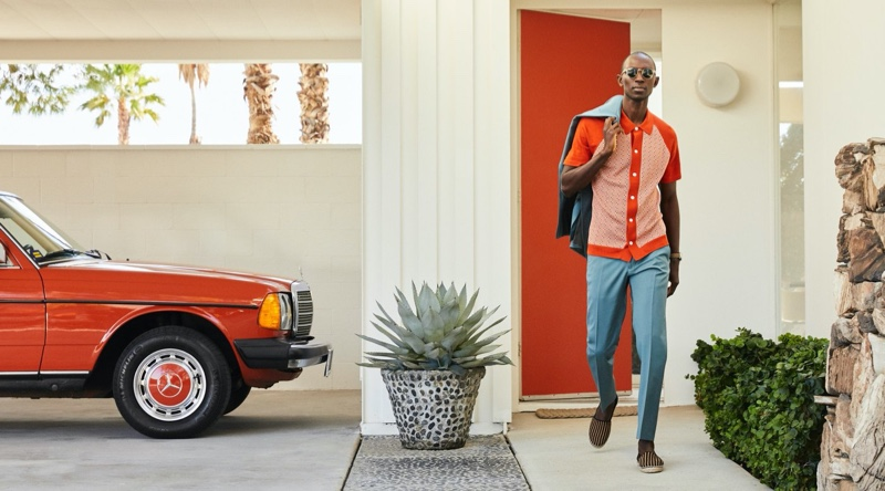 Armando Cabral dons a Todd Snyder Italian checkered polo in orange with a Sutton wool gabardine suit jacket and trousers. He also wears Guanabana striped espadrilles.