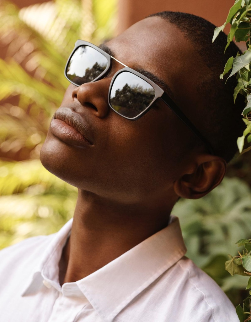 A thin sleek pair of sunglasses presents itself with Warby Parker's Drummond style in jet black matte with polished silver.