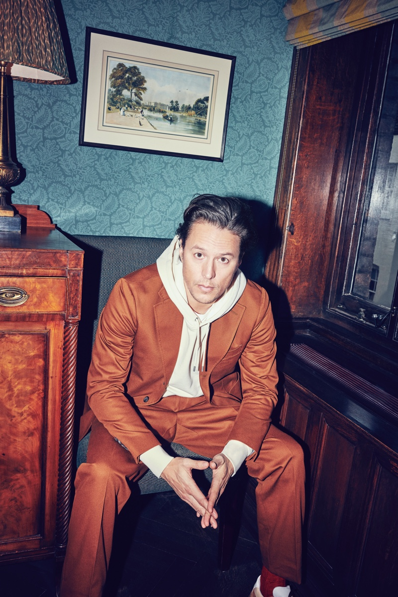 Adding a relaxed attitude to an Aimé Leon Dore + Drake's brown suit, Cary Joji Fukunaga also wears a Café Kitsuné cotton-jersey hoodie, and Acne Studios sneakers.