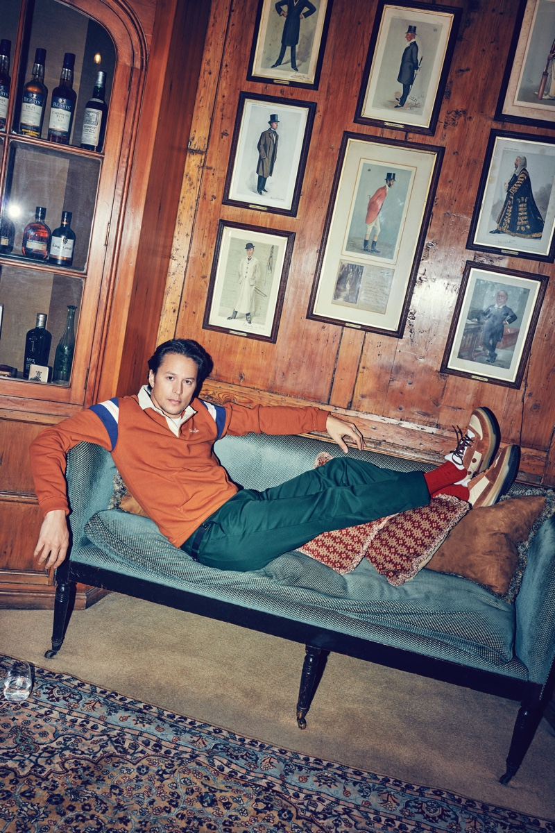 Relaxing, Cary Joji Fukunaga rocks an Aimé Leon Dore rugby sweatshirt, Paul Smith wool and mohair-blend suit trousers, and Acne Studios sneakers.