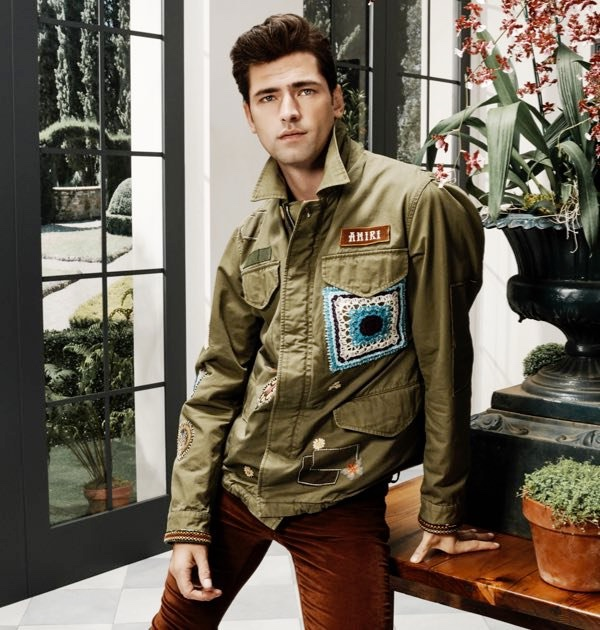 American model Sean O'Pry sports an AMIRI military short parka with the brand's velour skinny stack pants.