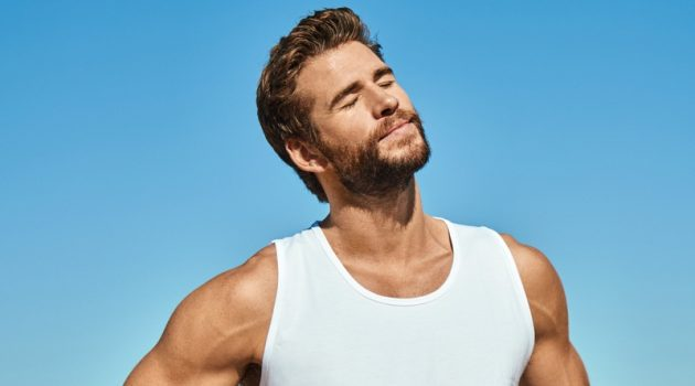 Connecting with Men's Health, Liam Hemsworth sports a Rawganique tank with Everlane pants.