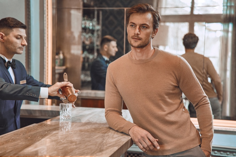 Craig Le Roux sports a brown cashmere sweater from Luca Faloni.