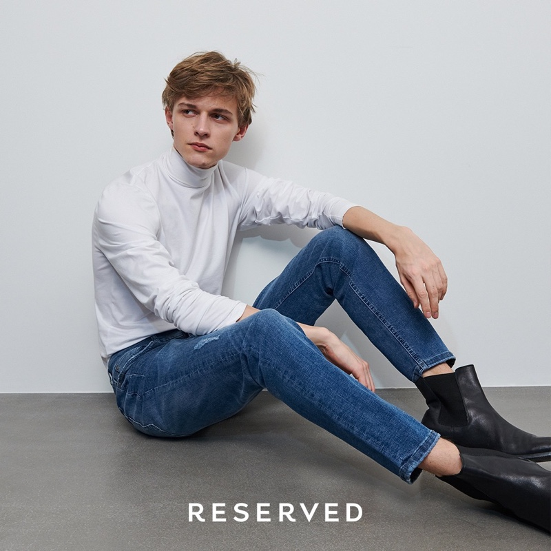 Max Barczak sports a white turtleneck with slim-fit jeans and black leather boots from Reserved.