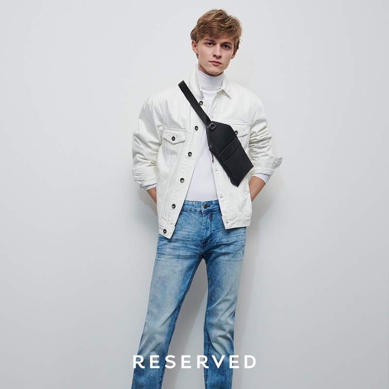 Mixing denim, Max Barczak wears a white trucker jacket and blue rinse jeans from Reserved.