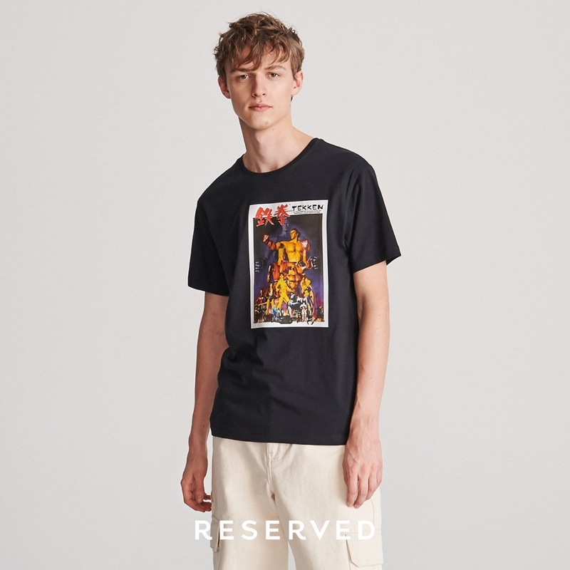 Embracing everyday casual wear, Max Barczak models a graphic t-shirt with cargo pants.