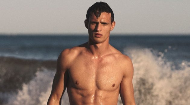 Julian Schneyder fronts Orlebar Brown's spring-summer 2020 campaign in a pair of the brand's Bulldog sunset silhouette mid-length swim shorts.