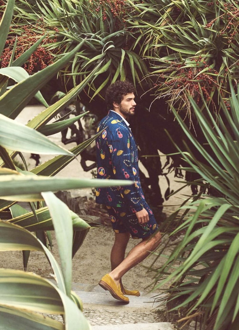 Donning an all-over print, Paul Kelly wears a matching suit jacket and chino shorts from Scotch & Soda.