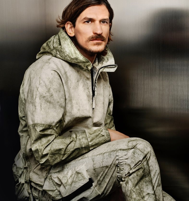 Jarrod Scott dons Stone Island's Membrana + Oxford 3l With Dust Color Finish anorak with cargo pants for Holt Renfrew.