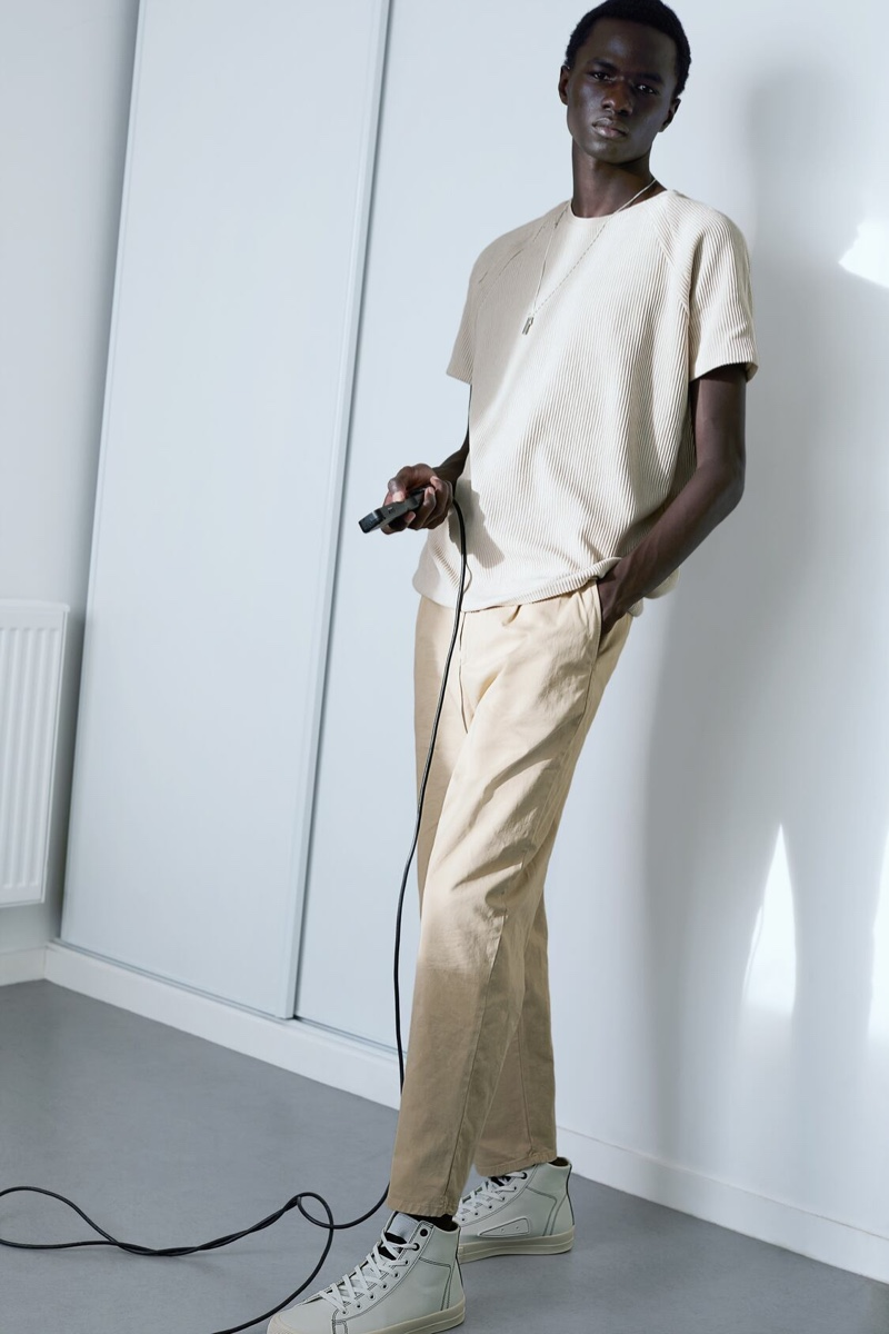 Posing for a photo, Malick Bodian dons a textured short-sleeve sweater with 1980s-inspired chinos by Zara.