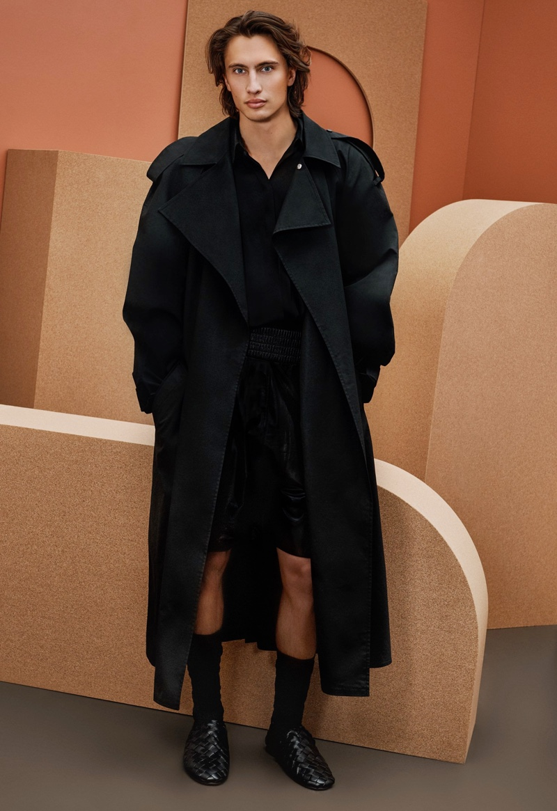 Front and center, James Turlington models a trench coat, long-sleeve shirt, leather shorts, and sandals from Bottega Veneta for Holt Renfrew.