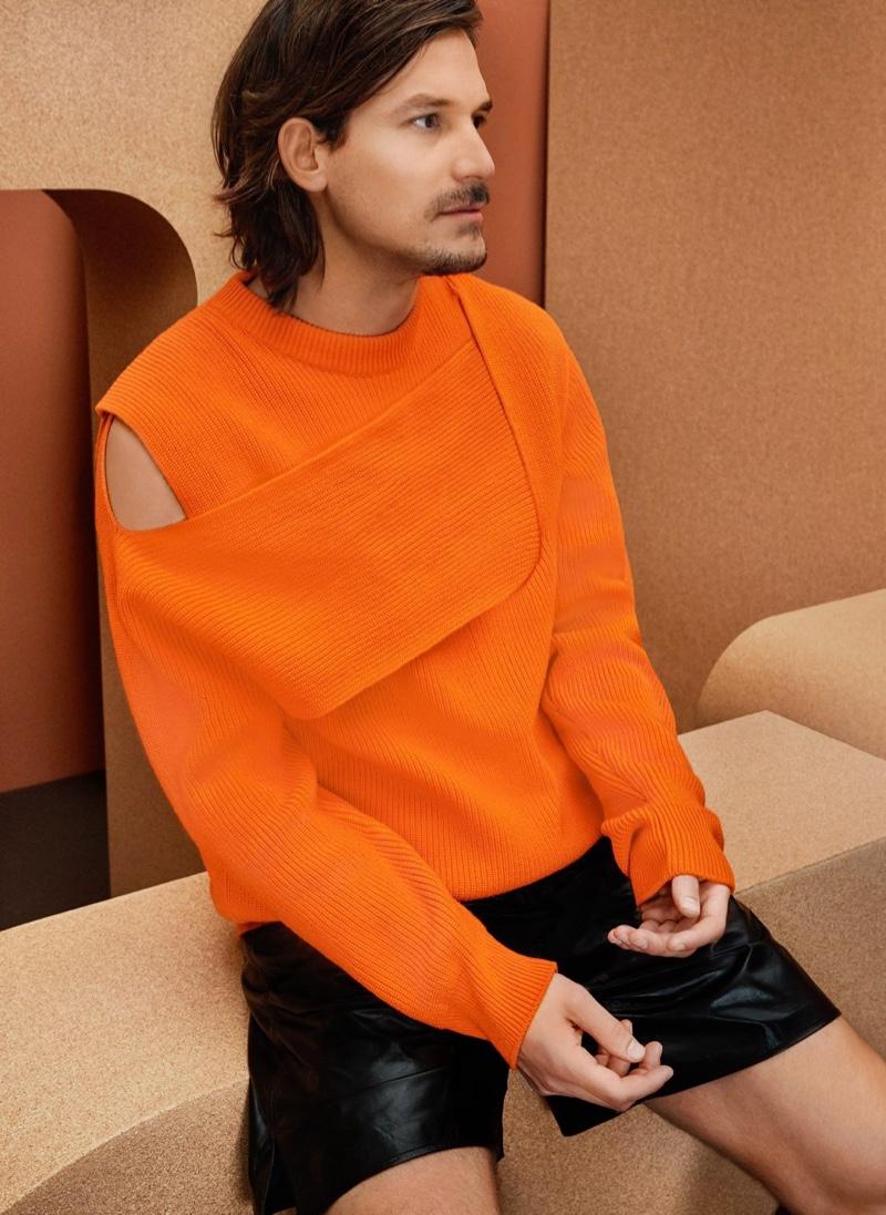 Embracing a pop of color in an orange cashmere sweater, Jarrod Scott also wears leather shorts from Bottega Veneta.