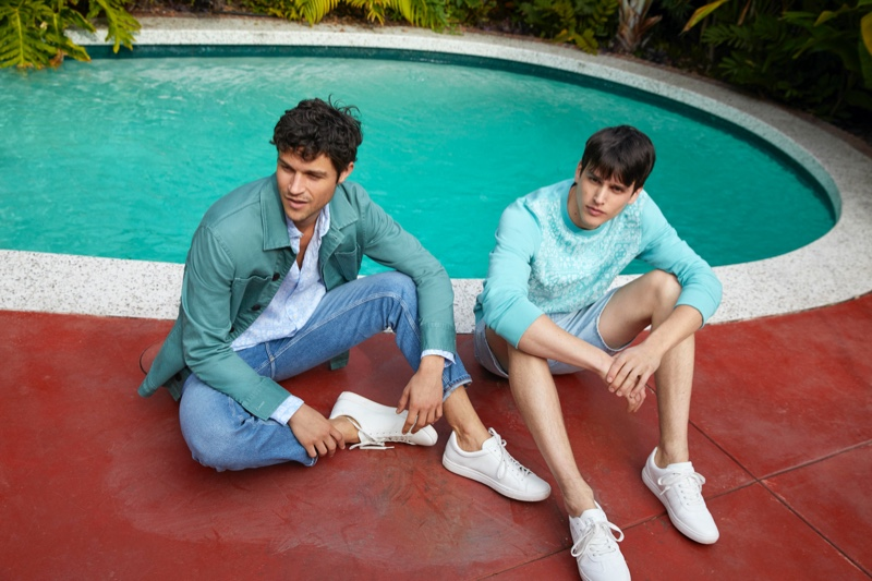 Models Miles McMillan and Simon Van Meervenne relax poolside in summer fashions from Esprit.